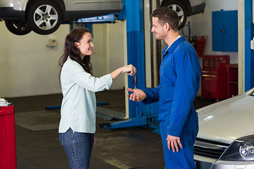 woman giving mechanic her keys to work on transmission